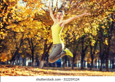 Young happy woman jumping in autumn park. Female fitness model training outside on a warm fall day. Sport lifestyle.