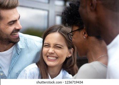 Young happy woman laughing at joke with multiethnic friends close up, African American couple having fun with caucasian colleagues, excited people in good relations, multiracial friendship concept