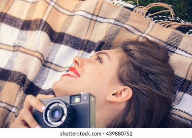 young happy woman laying with old film camera