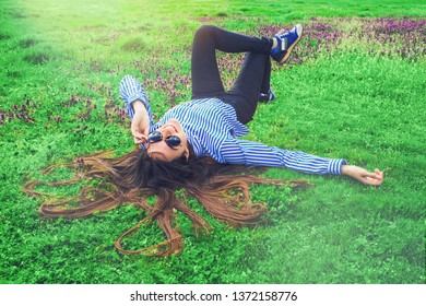 Young happy woman laying on green grass