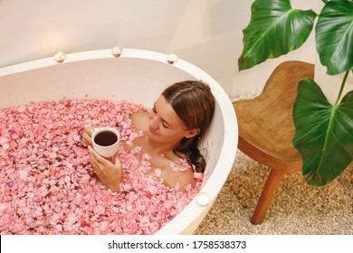 Young happy woman lie in bath tub full of pink roses flower petals drink herbal tea, enjoy her day in the spa. White bath tube with pink  tropical flowers petals, spa, relaxation, body care, therapy