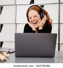 Young happy woman listening to music with headphones while sitting in front of laptop
