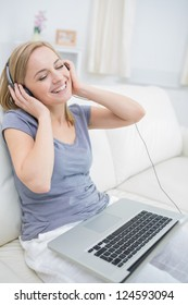 Young happy woman listening music through headphones with laptop in living room