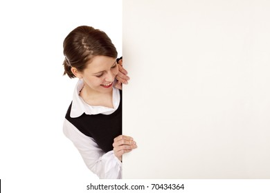 Young happy woman looks at blank ad space. Isolated on white background.