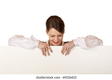 Young happy woman looks down on blank board. Isolated on white background.