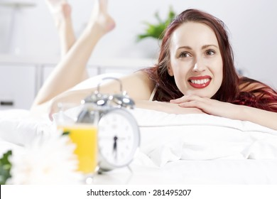 Young happy woman lying in bed and smiling