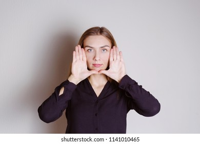 Young happy woman making a face and showing her palms