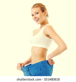 Young happy woman measuring waist with a tape measure in old jeans, health and dieting concept