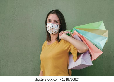 Young happy woman with medical mask holding a shopping bags over green background