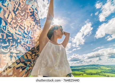 Young happy woman in mountain with fabric. Summer picnic. Happy woman enjoying nature and sunlight.
