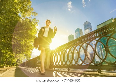 Young happy woman in office dress walking in the park with coffee cup and bag with skyscrapers on background with sunbeam blur.