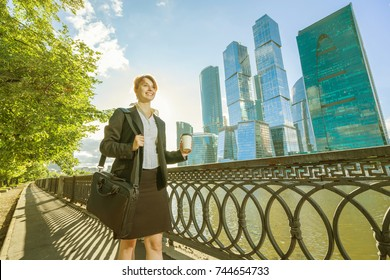 Young happy woman in office dress walking in the park with coffee cup and bag with skyscrapers on background.