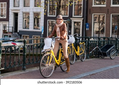 Young happy woman on bicycle in european city, Amsterdam, Netherlands