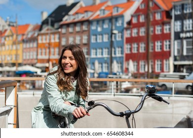 Young happy woman on bicycle at the Nyhavn harbor pier in european city Copenhagen, Denmark, looking at camera and smiling. Visiting Scandinavia, famous European place.
