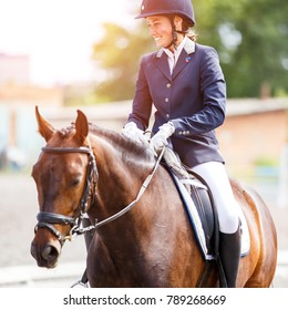 Young happy woman on her bay horse after dressage test on equestrian competitions