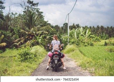 Young happy woman on a motorbike in the jungle rainforest of a tropical Bali island, Indonesia. Freedom concept.