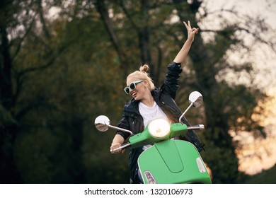 A young and happy woman on a scooter. She drives through the forest with two fingers in the air.