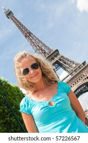 Young happy woman in Paris with Eiffel tower in background