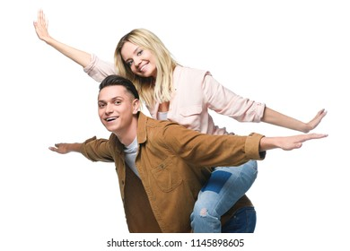 young happy woman piggybacking on boyfriends back and looking at camera isolated on white