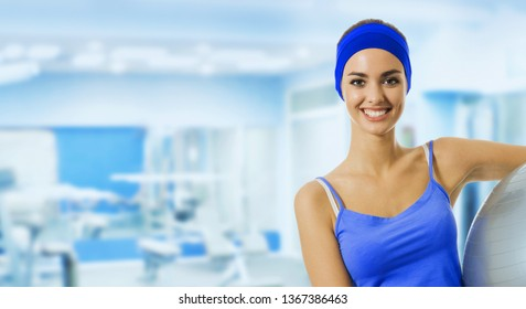 Young happy woman with pilates ball, at fitness club or center, with blank copyspace area for slogan or text