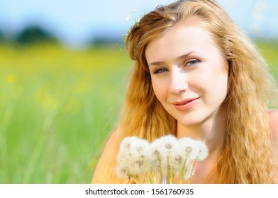 Young happy woman posing with dandelions in her hands and flowers in her hair. Beautiful portrait photo in a flower field