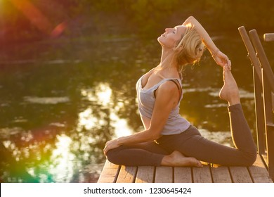 Young happy  woman  practicing yoga in nature
