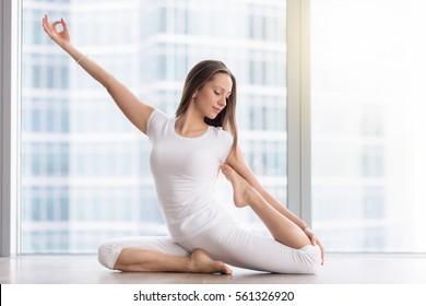 Young happy woman practicing yoga, sitting in One Legged King Pigeon exercise, Eka Pada Rajakapotasana pose, working out, wearing sportswear, white t-shirt, pants, indoor full length