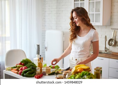 Young happy woman preparing tasty salad in the beautiful kitchen with green fresh ingredients indoors. Healthy food and Dieting concept. Loosing Weight