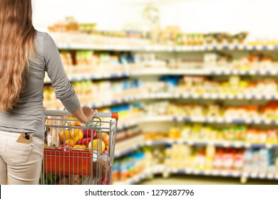 Young happy woman pushing shopping cart