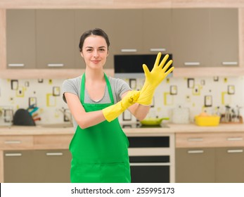 young happy woman putting rubber gloves and getting ready for cleaning