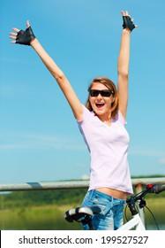 Young happy woman raised hands up in joy, outdoor shoot