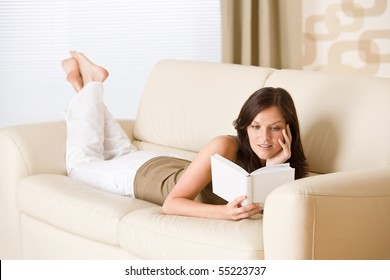 Young happy woman read book on sofa in living room