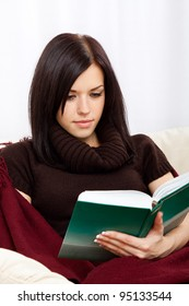 Young happy woman read book on sofa in living room, wearing knitted brown sweater, at home - indoors covered with blanket