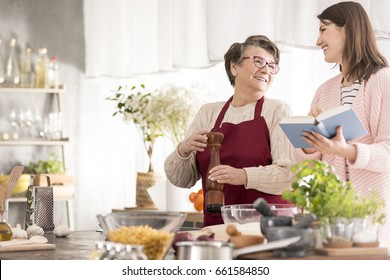 Young, happy woman reading grandmother recipes, cooking together