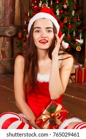 Young happy woman in red santa hat and red dress sitting near new year tree with present