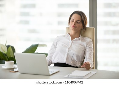 Young happy woman relaxing enjoying break feeling no stress free relief after computer work, meditating with eyes closed, resting leaning on comfortable ergonomic office chair breathing fresh air