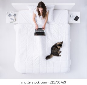 Young happy woman relaxing in her bed with her pet, she is connecting with a laptop, top view