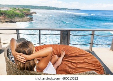 Young happy woman relaxing in lounge on roof veranda with beautiful tropical sea view. Positive girl look at ocean surf, enjoy vacation. Healthy lifestyle, people on family summer beach holiday.
