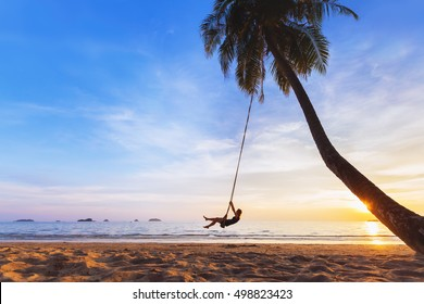 Young happy woman relaxing on a swing attached to a palm tree on a paradise beach at sunset while on vacation in a tropical country