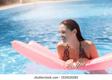 Young happy woman relaxing in swimming pool on pink inflatable mattress, looking away, has happy facial expression, dark haired girl enjoying summer vocation.