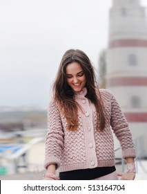 Young happy woman romantic portrait, looking down and smiling, dressed in cute gentle pink sweater, autumn fashion, sea and lighthouse in the background