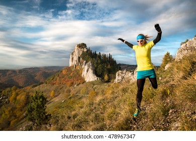 young happy woman running and jumping fast on mountain trail in autumn nature with blue sky and peak view