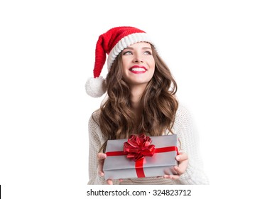 394117ede058f Young happy woman in santa hat looking sideways showing Christmas present  isolated on white background.