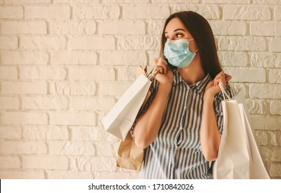 Young happy woman shopaholic in medical face mask hold shopping bags and looking at copy space. Beautiful girl in medical face mask with paper bags. Woman shopper, sale, discount, coronavirus COVID-19