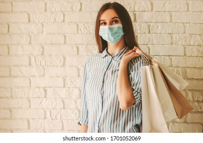 Young happy woman shopaholic in protective mask on face with paper bags in hands. Beautiful girl in medical face mask hold shopping bag. Woman shopper. Copy space. Coronavirus COVID-19, sale, discount