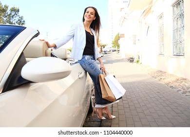 Young happy woman with shopping bags near the car outdoors