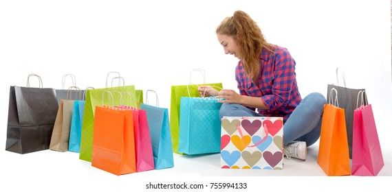 Young happy woman with shopping bags, isolated on white background