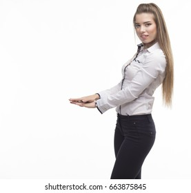 Young happy woman showing height on a gray background. Ideal for banners, registration forms, presentation, landings, presenting concept.