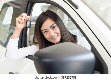 Young Happy Woman Showing The Key Of her New Car, Dream comes true concept