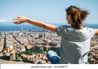Young happy woman sits back to the camera with raised hands. Traveler enjoying the cityscape of mountain, Barcelona, Catalonia, Spain